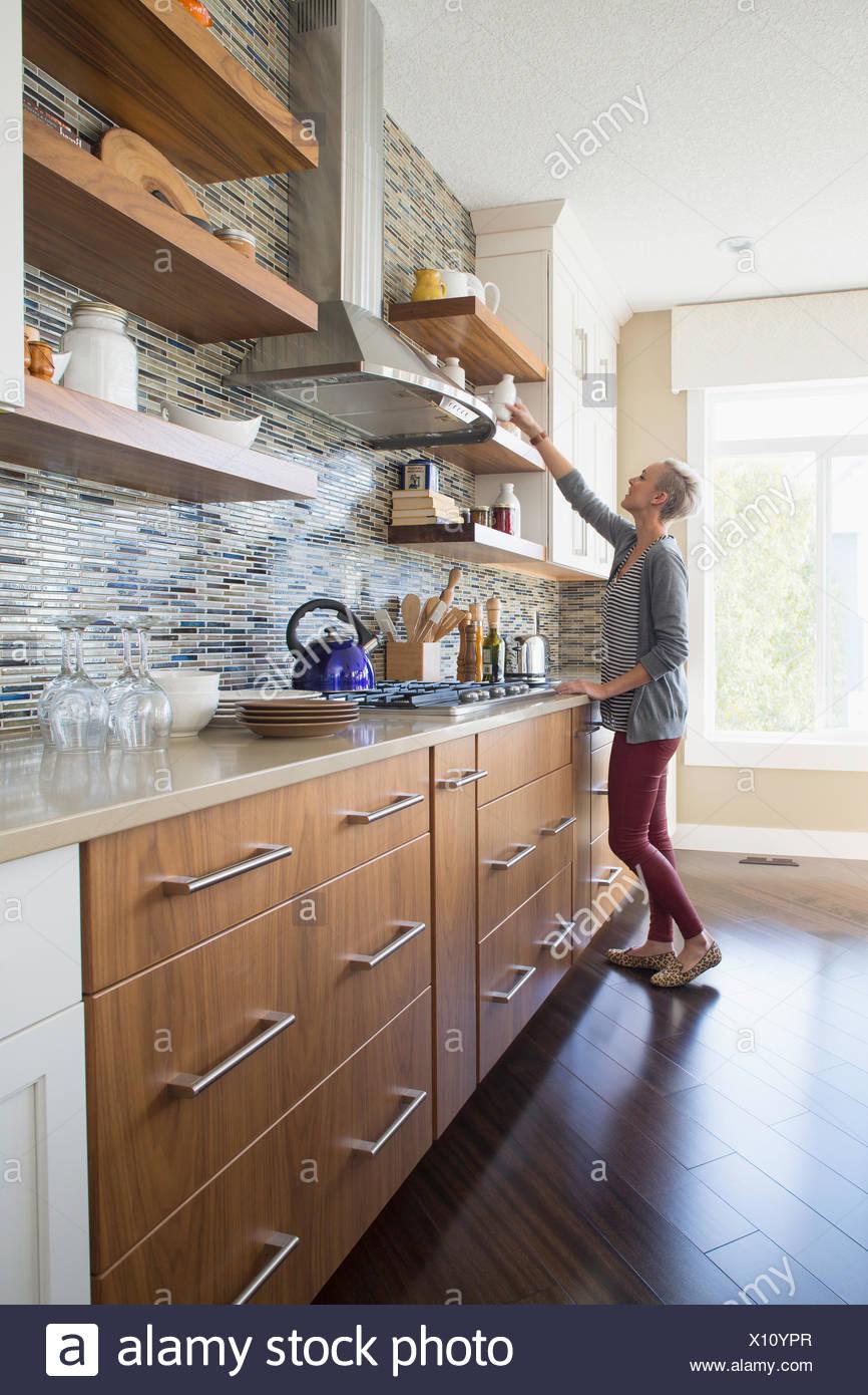 Woman reaching for jar on kitchen shelf - Stock Image