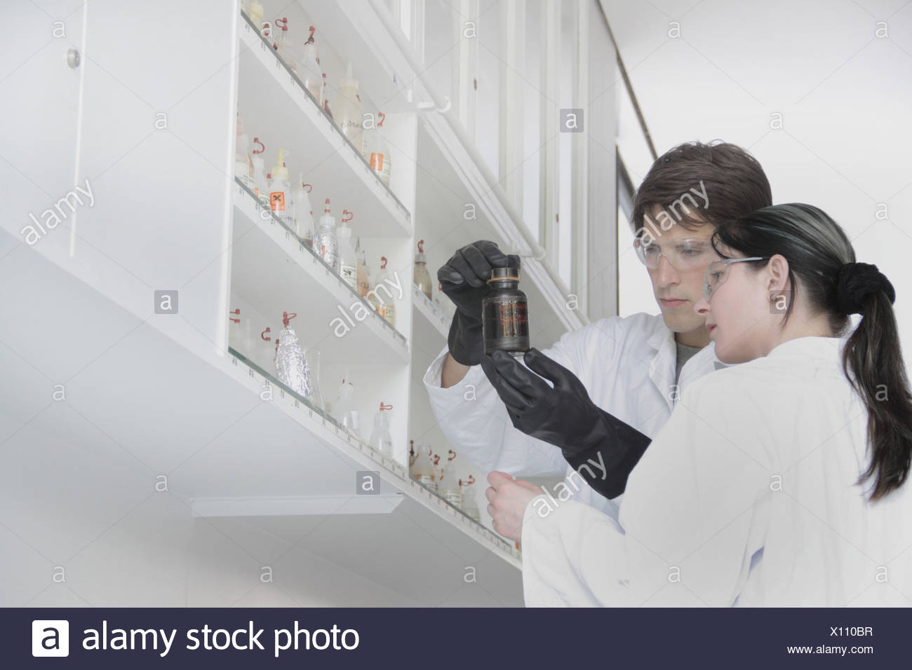 Chemistry students looking at container in lab - Stock Image