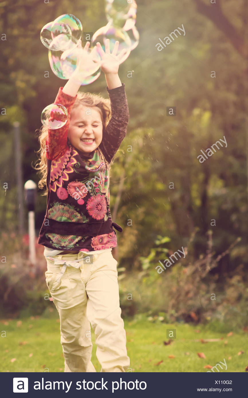 Girl outdoors trying to catch soap bubbles - Stock Image