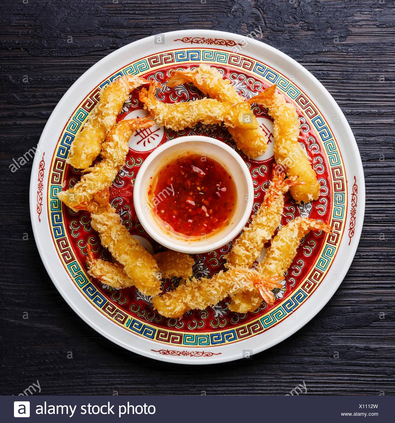 Deep fried breaded Tempura prawn shrimps with sauce on black burned wooden background - Stock Image