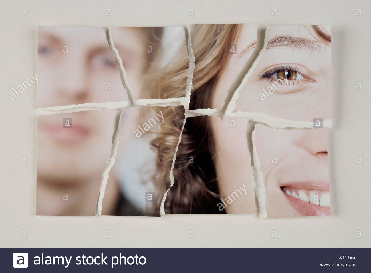 A photograph of a heterosexual couple torn into pieces - Stock Image