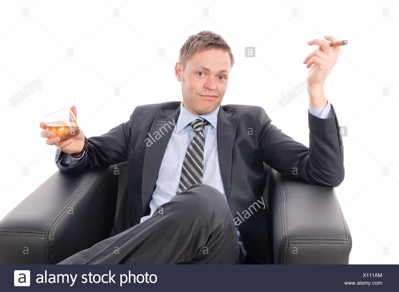 Junger Geschäftsmann in Anzug und Krawatte sitzt gemütlich in einem schwarzen Ledersessel und genießt eine Zigarre und einen Drink. Freigestellt vor weißem Hintergrund - Stock Image