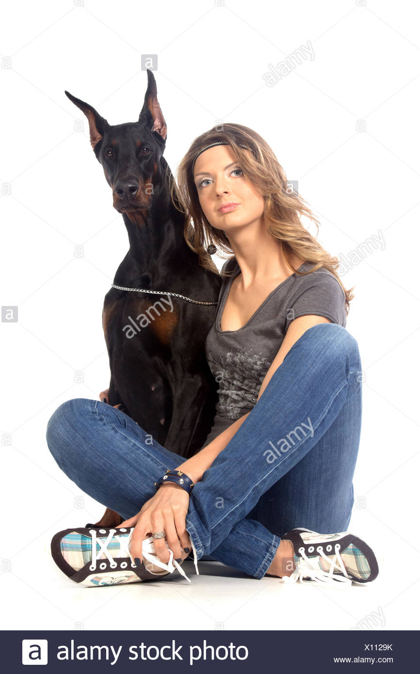 Young woman with black dobermann dog - Stock Image