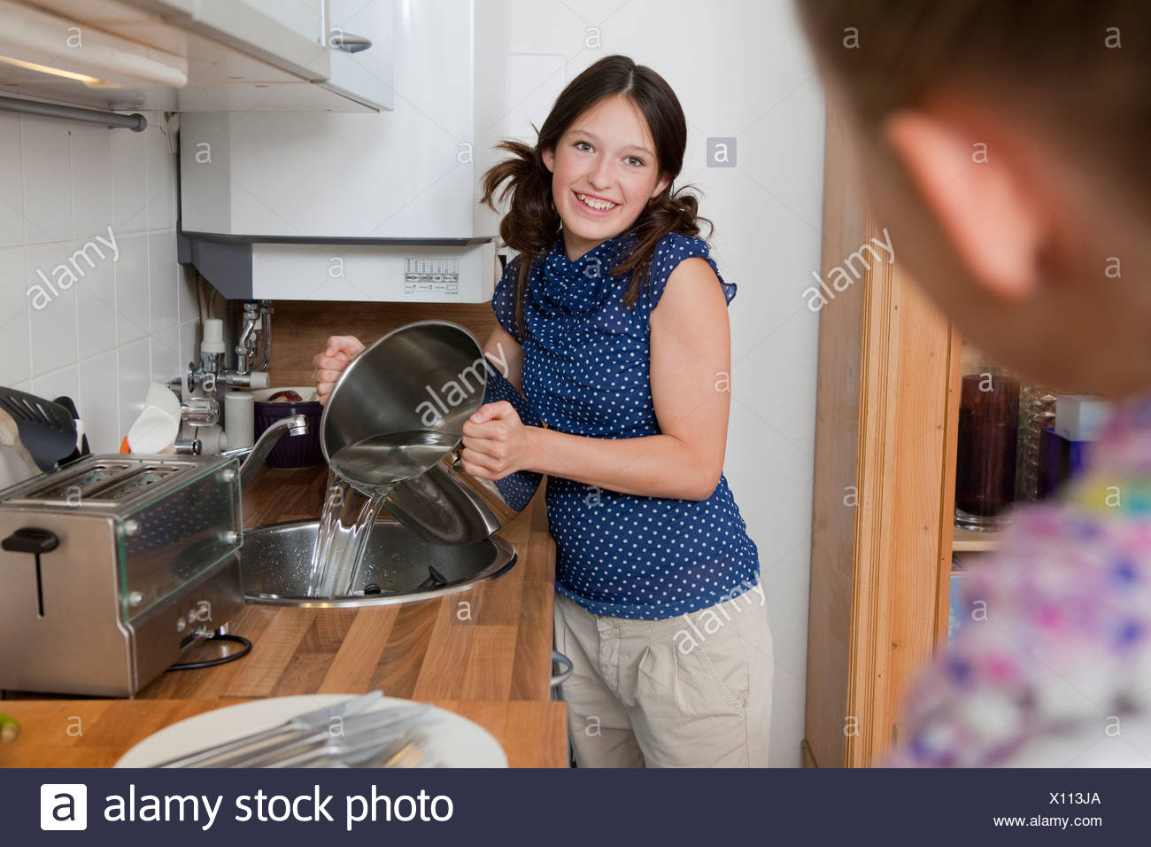 Smiling girl draining water from pot - Stock Image