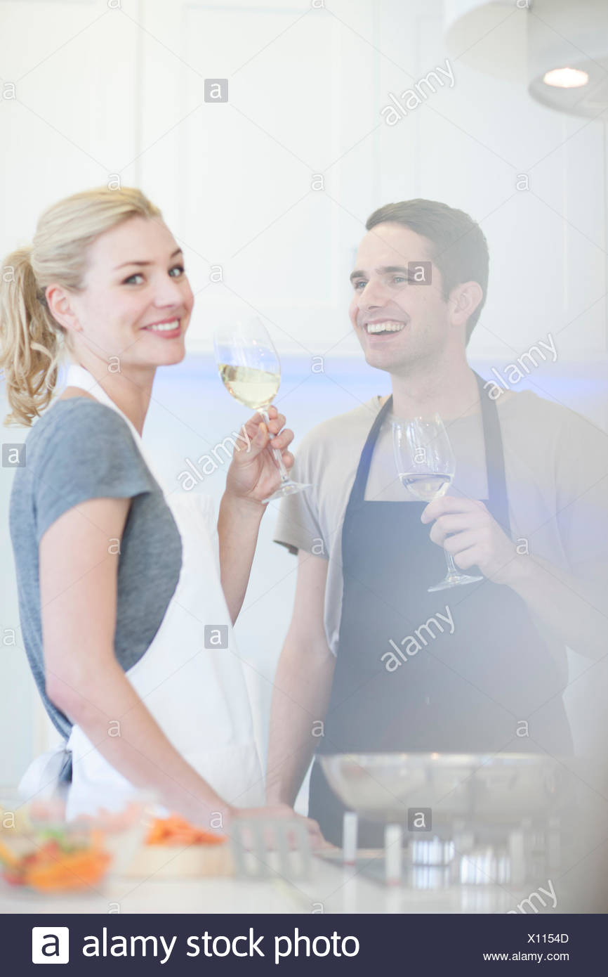 Couple preparing food and drinking glass of white wine in kitchen Stock Photo
