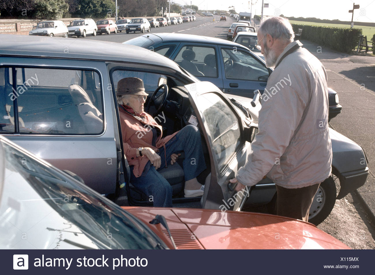elderly son assisting mother out of the car Stock Photo
