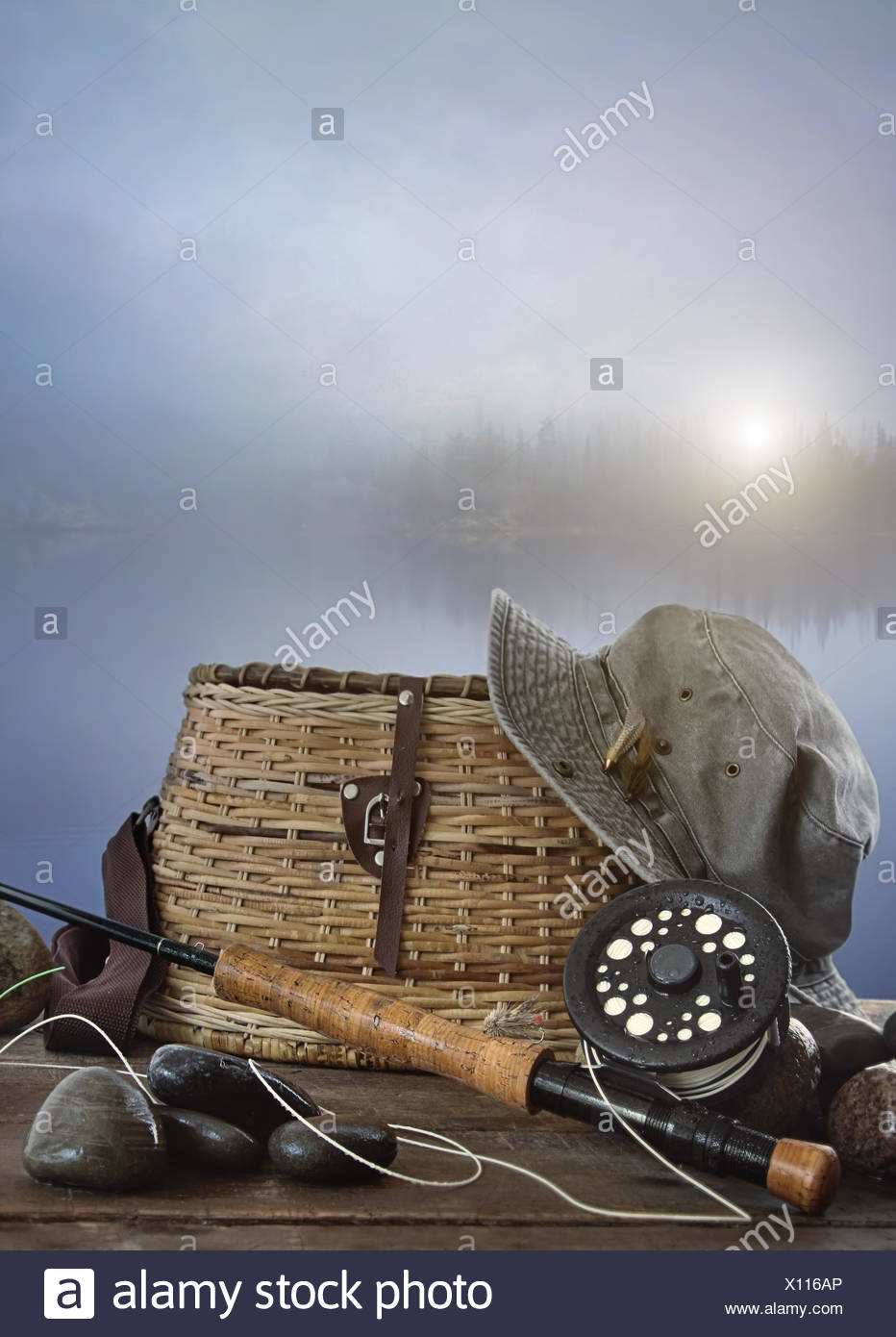 Fly rod with creel and equipment on wood table Stock Photo