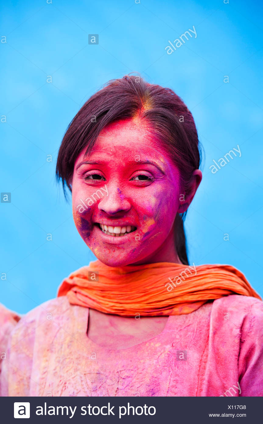Smiling woman with her face smeared with colors Stock Photo