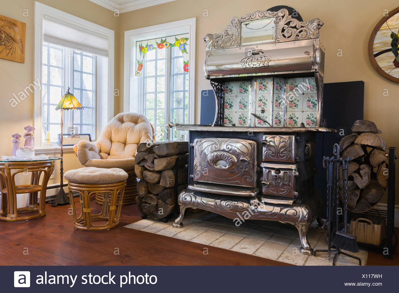 Antique black cast iron and chrome Royal wood burning cook stove in the family room inside an old reconstructed 1886 Canadiana cottage style residential home, Quebec, Canada - Stock Image