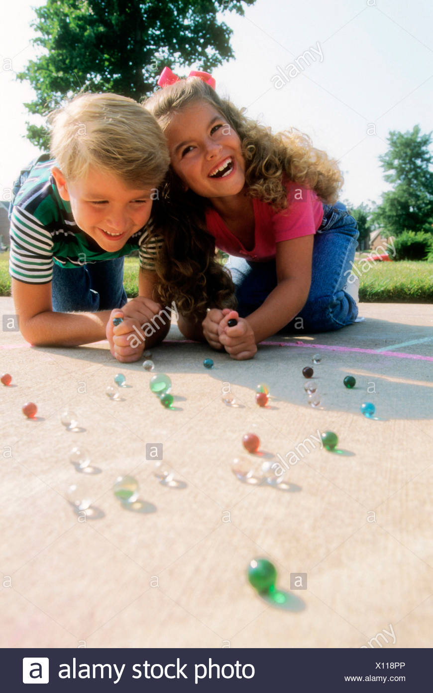 Kids playing marbles. - Stock Image