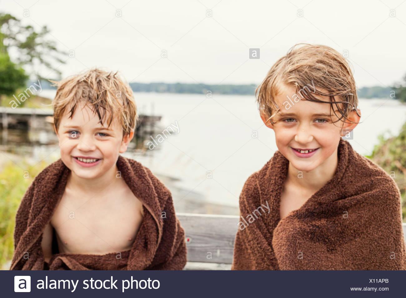 Sweden, Uppland, Runmaro, Barrskar, Portrait of two boys wrapped into towels - Stock Image