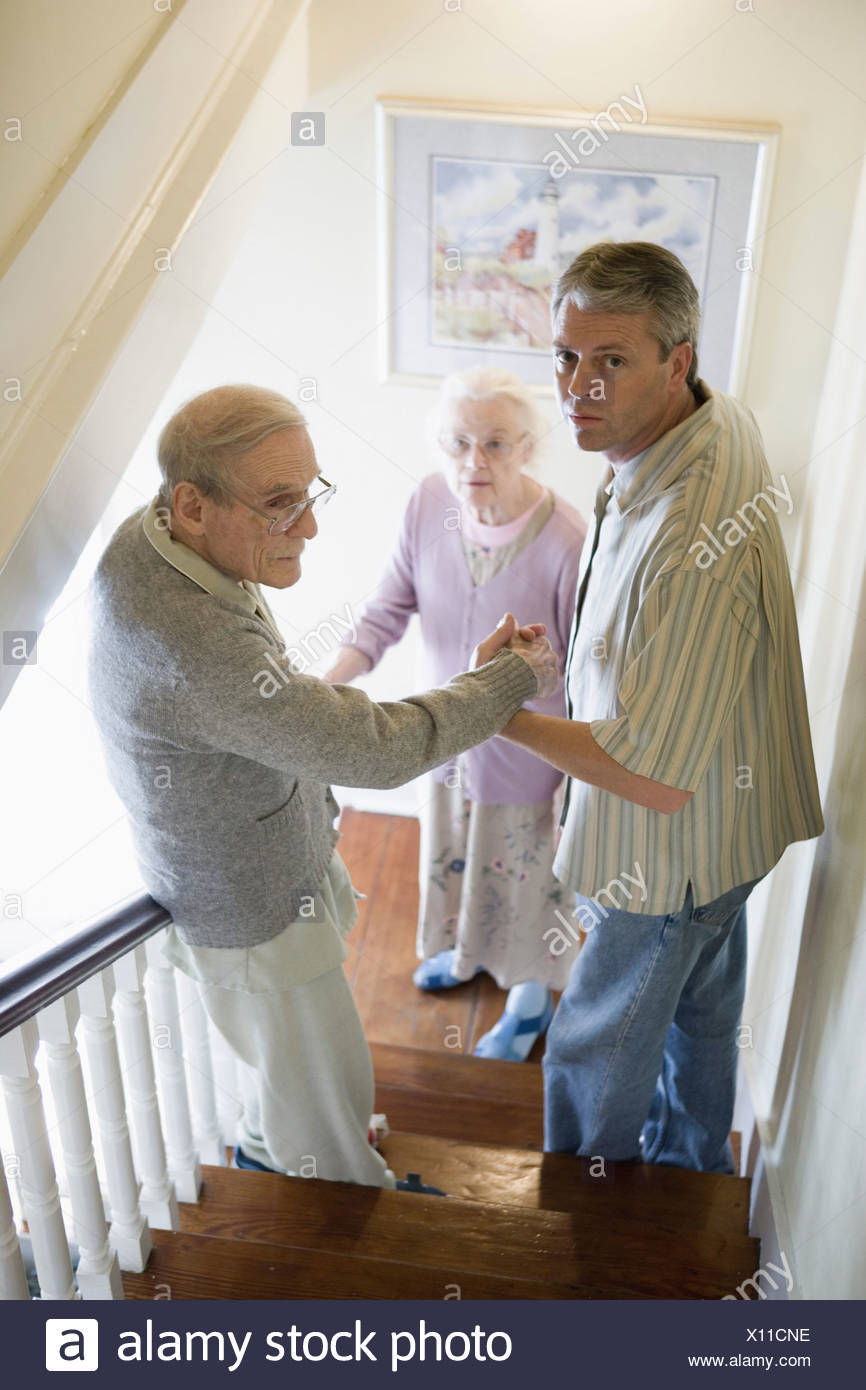 Man helping elderly man down the stairs while senior woman watches downstairs Stock Photo
