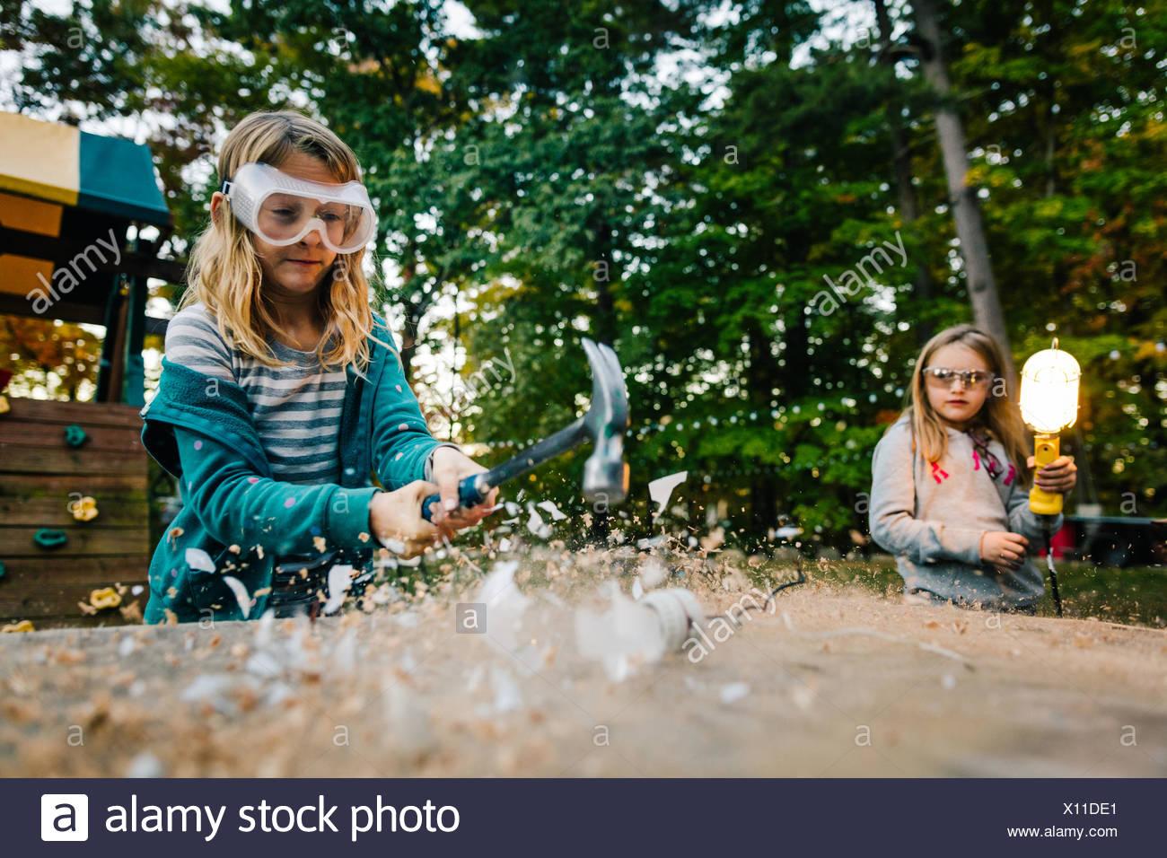 Girl smashing lightbulb with hammer on garden table at dusk - Stock Image