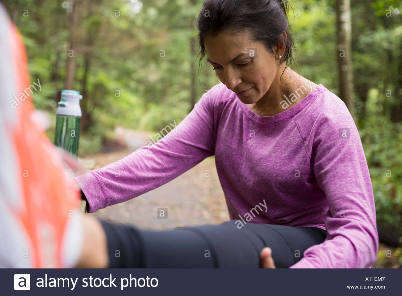 Woman stretching leg preparing for run in woods - Stock Image