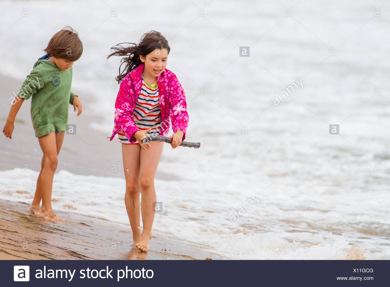 Boy and girl walking on the beach Stock Photo