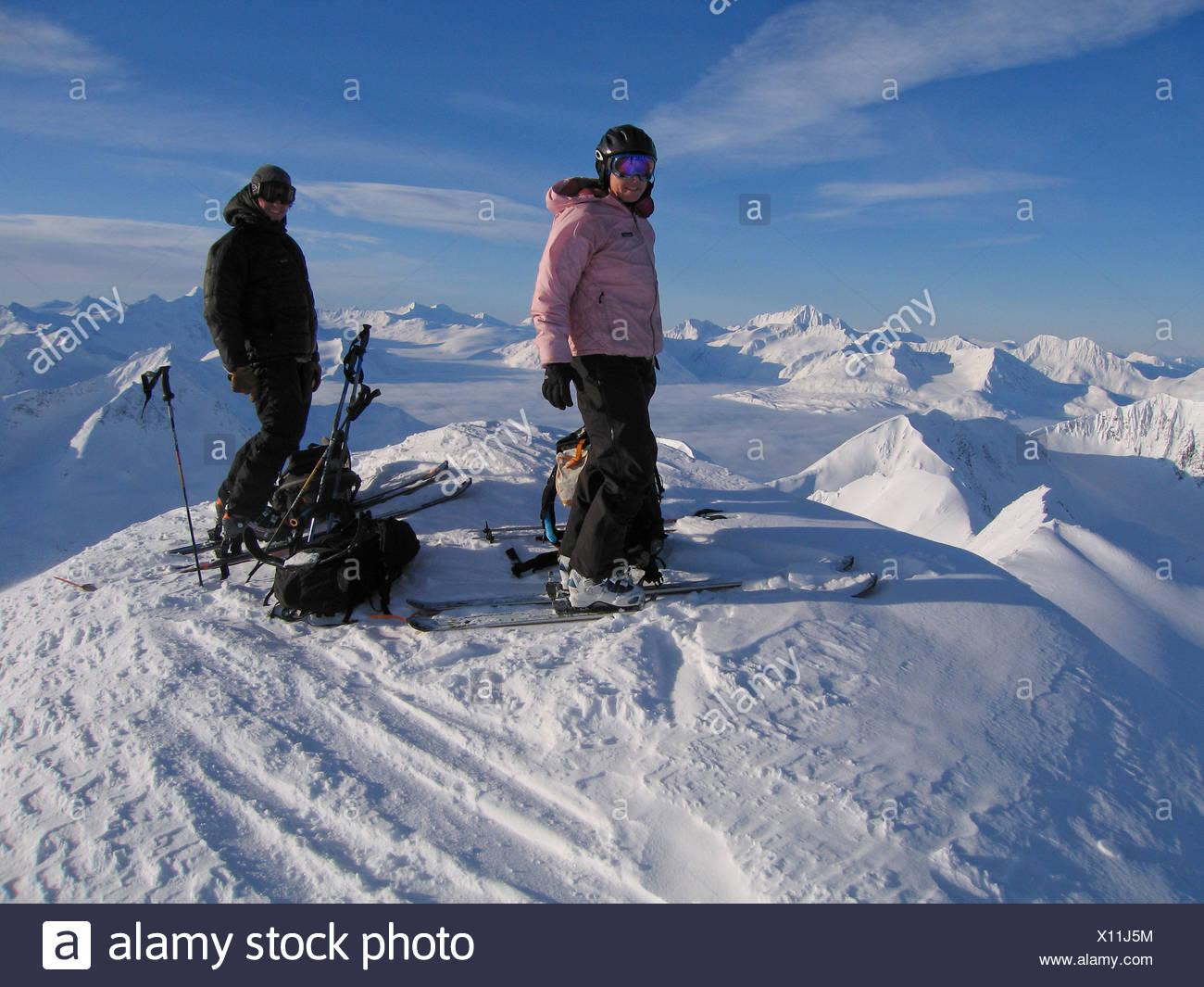 Backcountry skiers on top of a peak on Turnagain Pass, Alaska - Stock Image