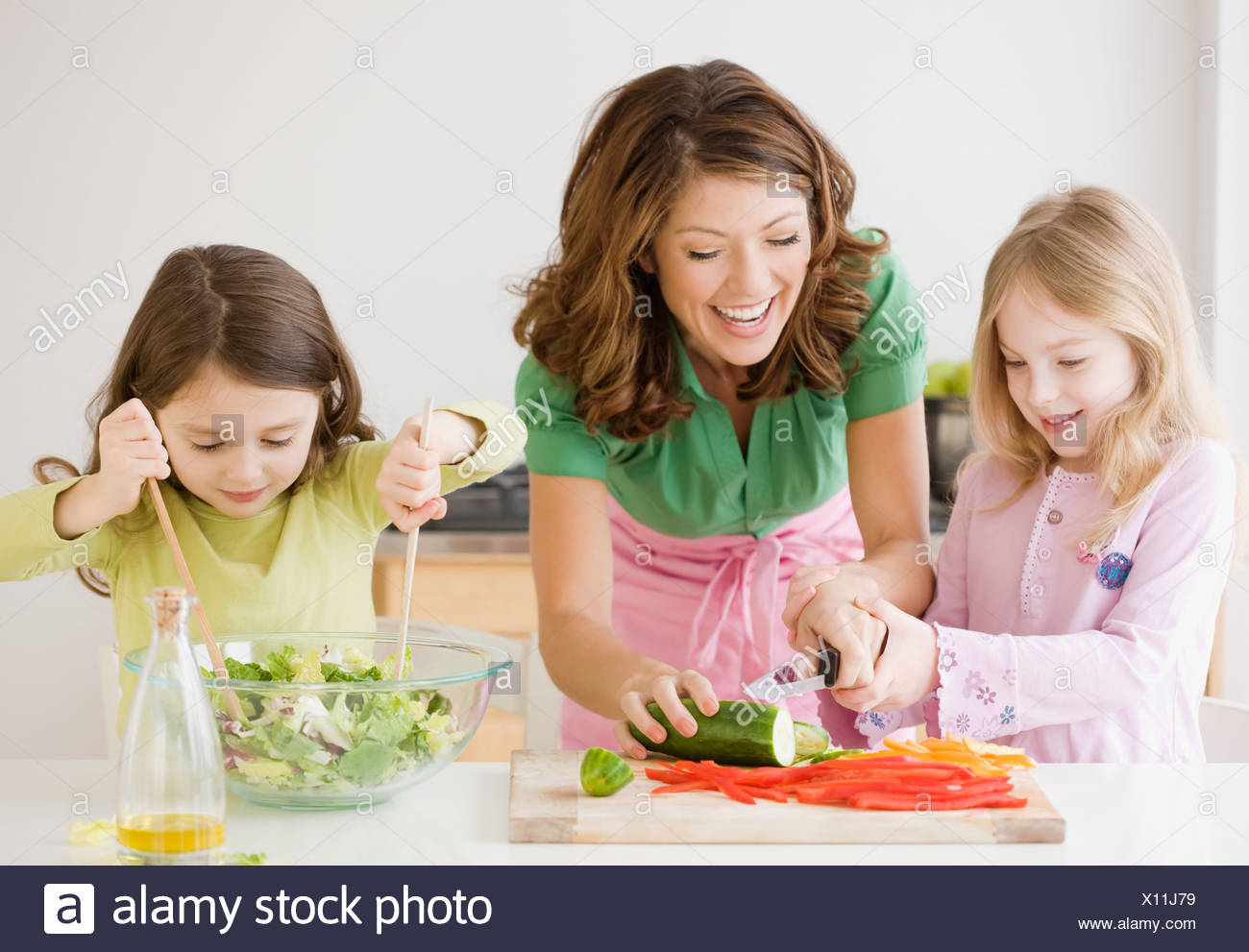 Mother and daughters preparing food - Stock Image