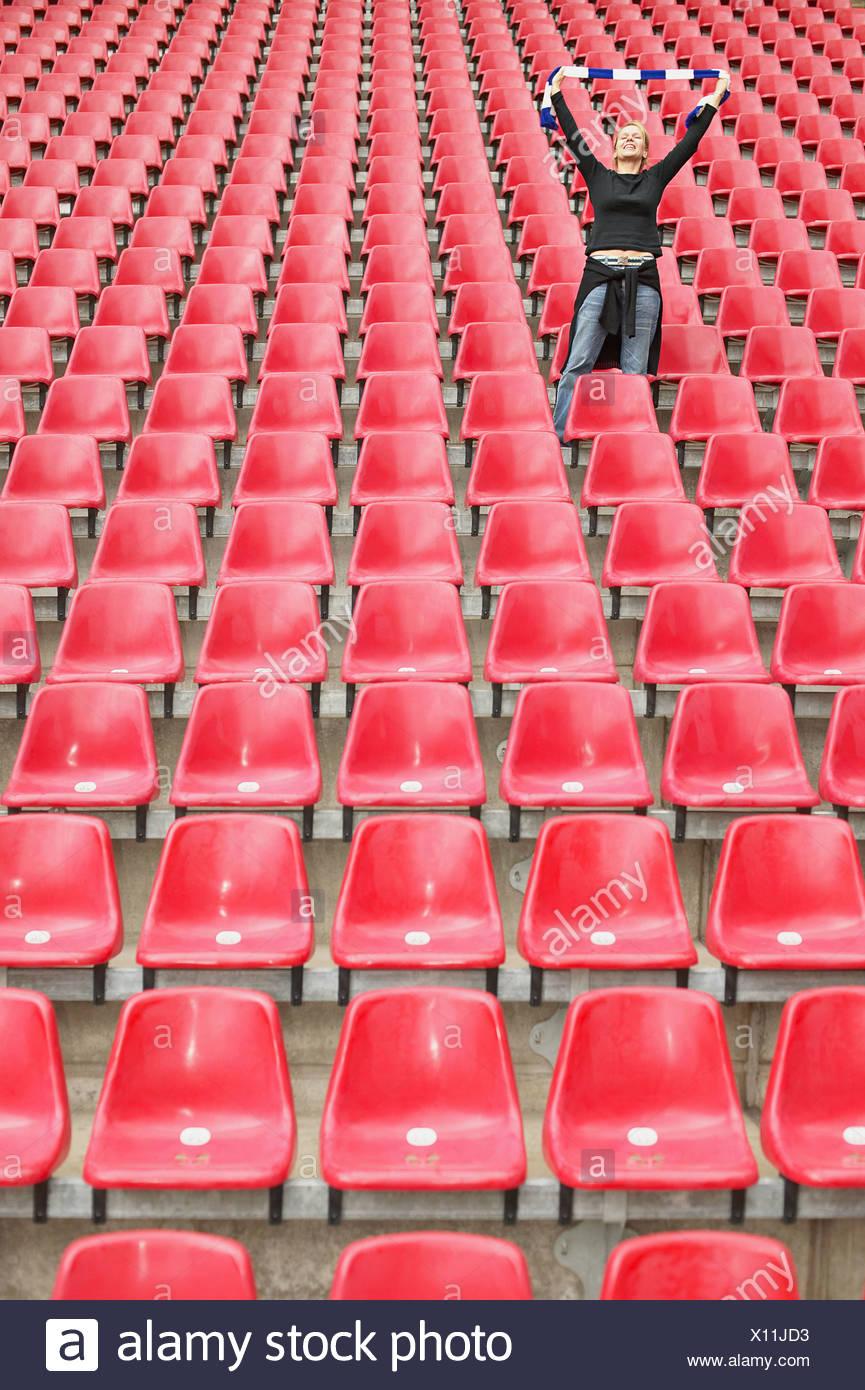 Female football fan alone in stadium - Stock Image