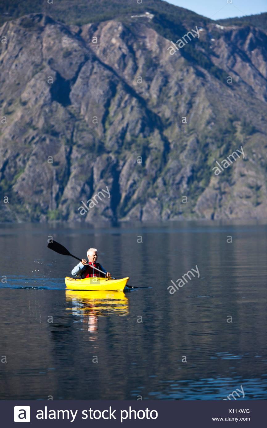 An adventurous retired man kayaking across a huge calm lake in Idaho. - Stock Image