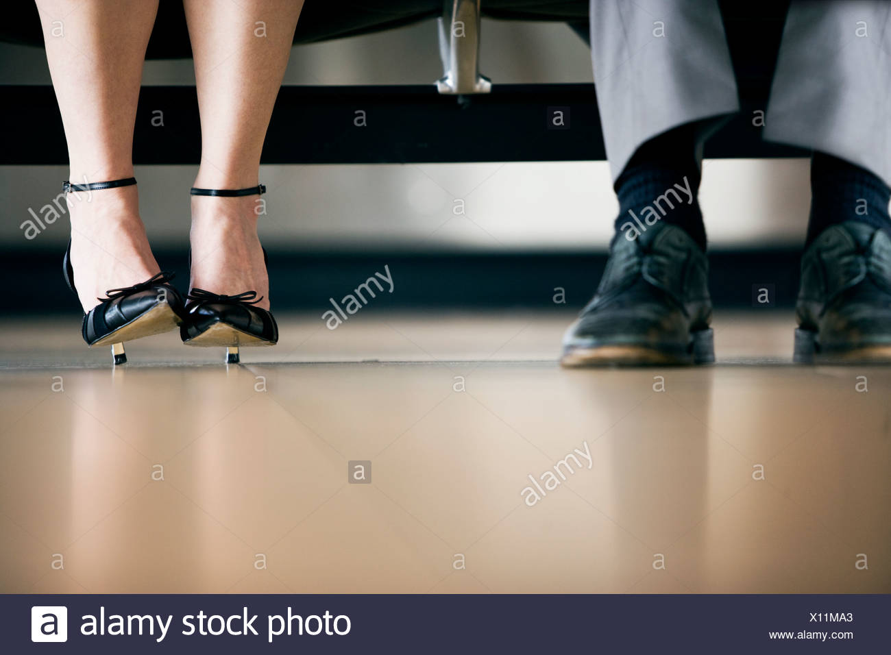 Close up of menís shoes and fashionable womenís high heels - Stock Image