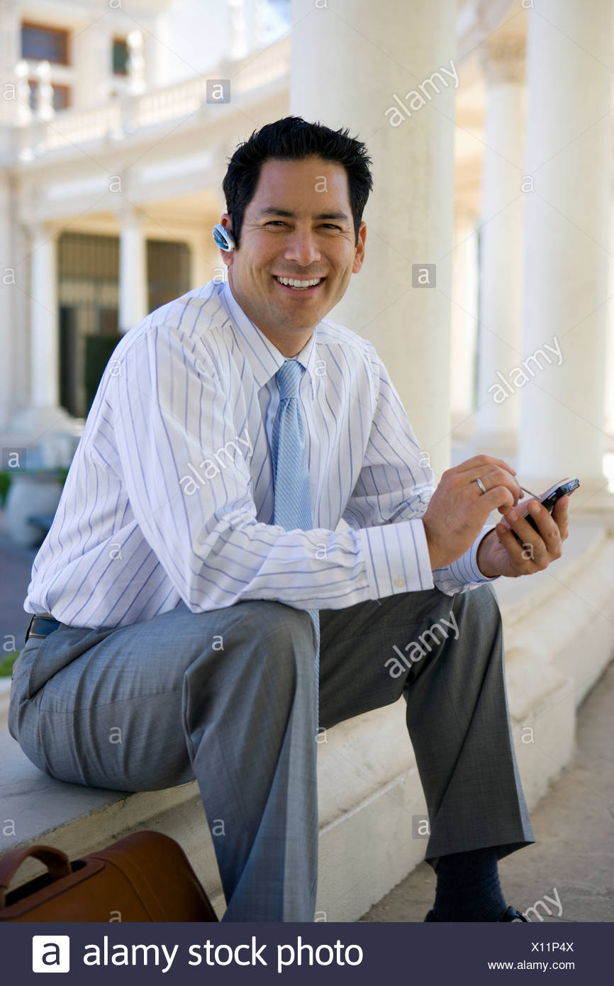 Businessman using hands free device outdoors - Stock Image