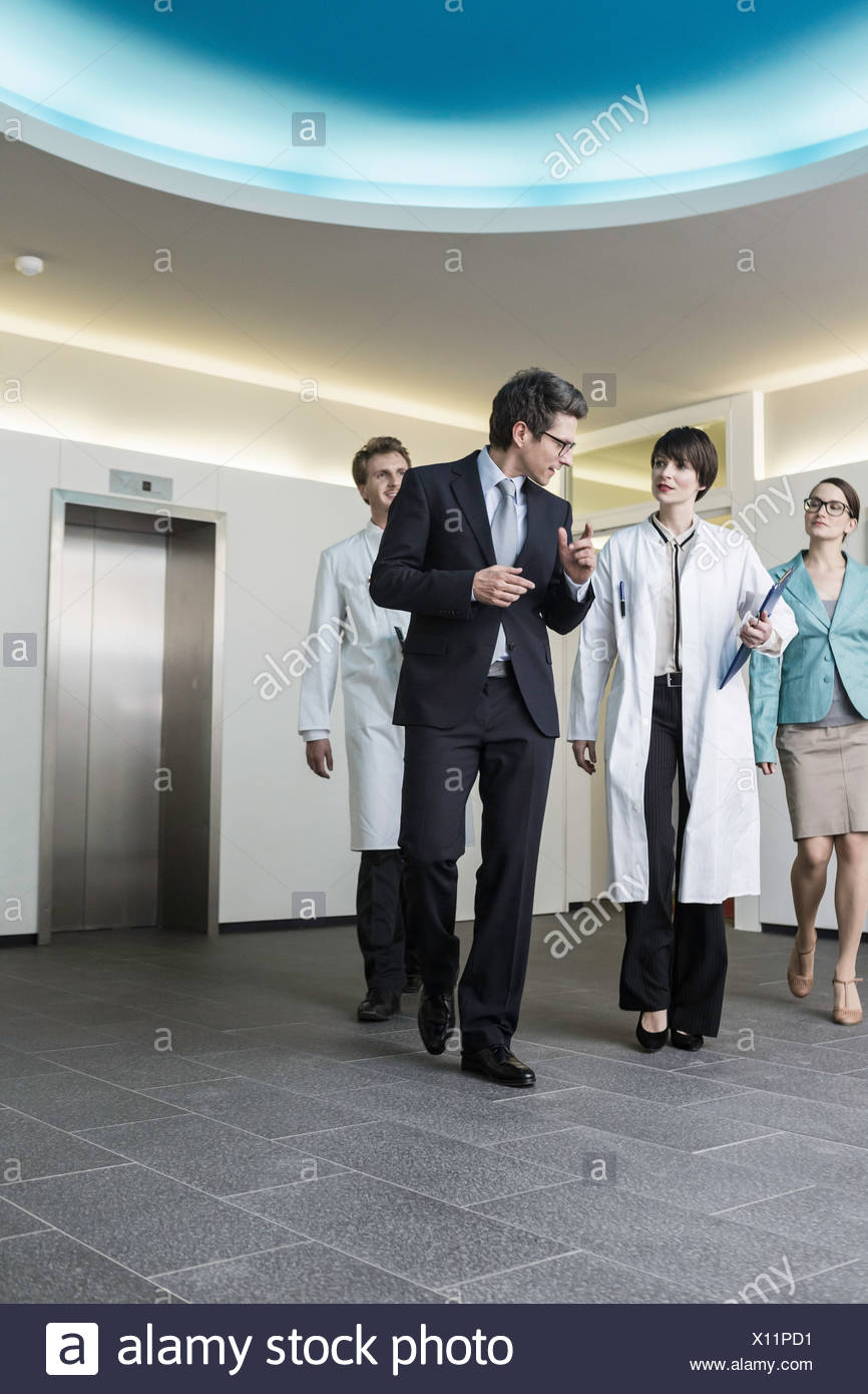 Four mid adults walking through lobby - Stock Image