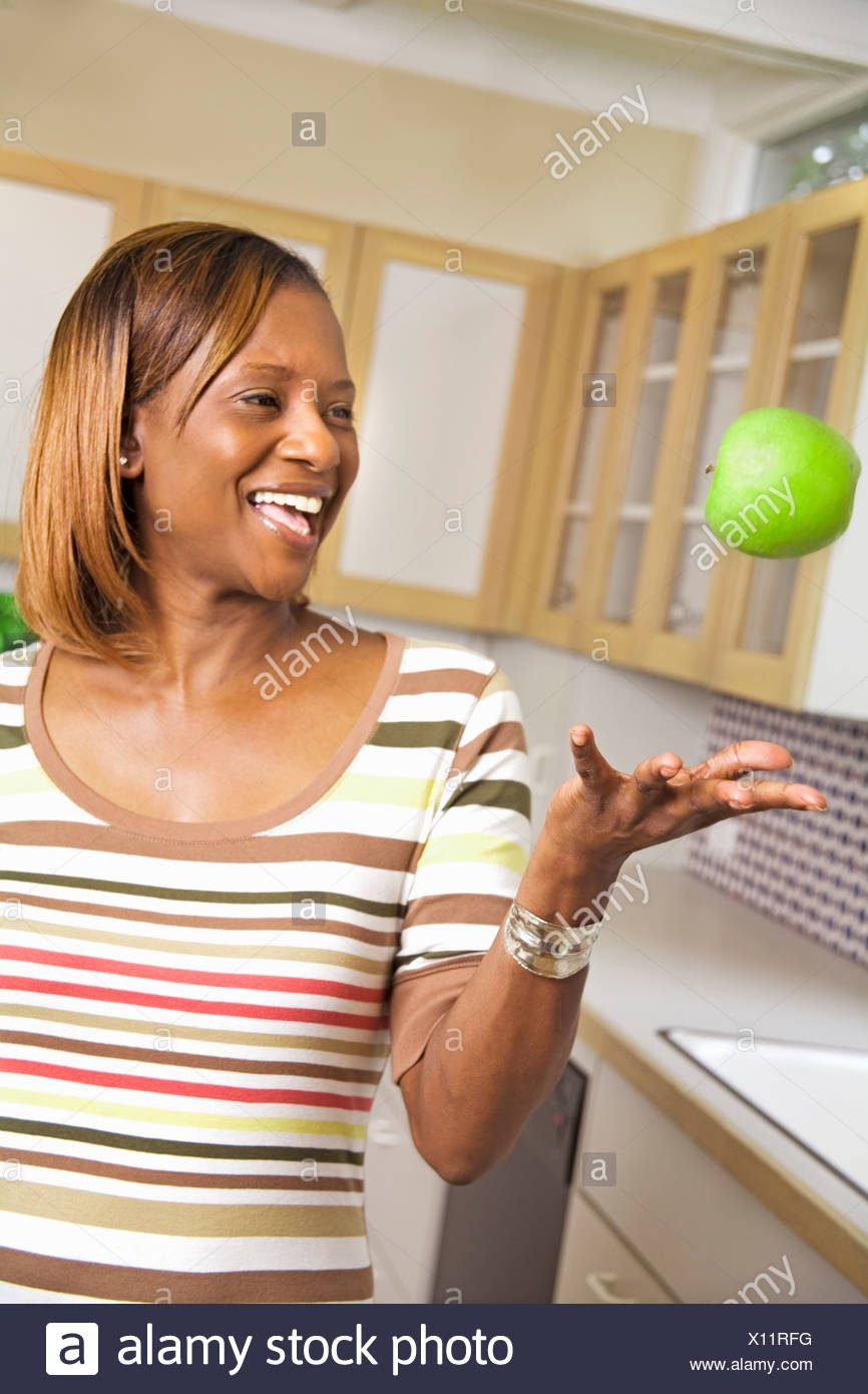 African woman throwing apple - Stock Image