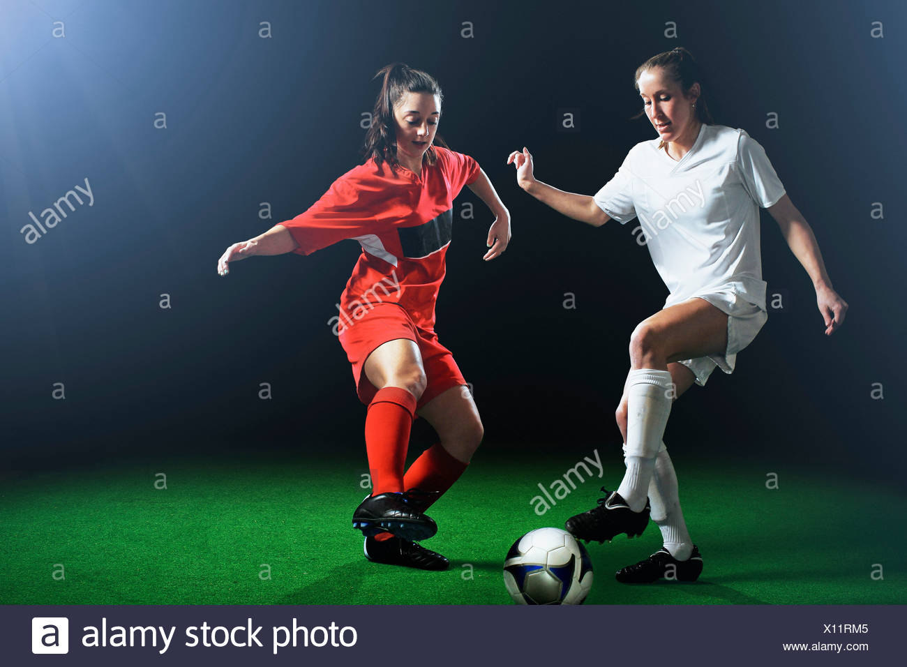 Two female soccer players tackling ball Stock Photo