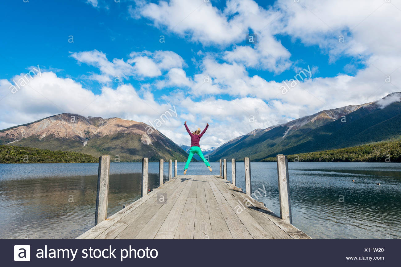 Woman jumping in the air, dock on Lake Rotoiti, Nelson Lakes National Park, Tasman District, Southland, New Zealand - Stock Image