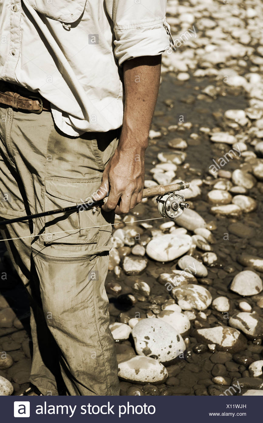 A fisherman holds his fly fishing rod on his side with white river rocks behind him. - Stock Image