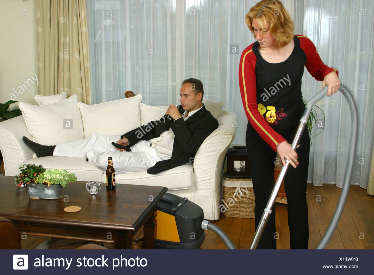 Housewife doing conventional housework and man resting after work - Stock Image