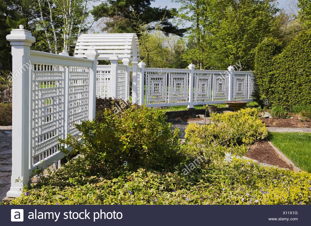 A White Wooden Fence With Trellis In A Landscaped Back Yard Garden In Spring;Quebec Canada Stock Photo