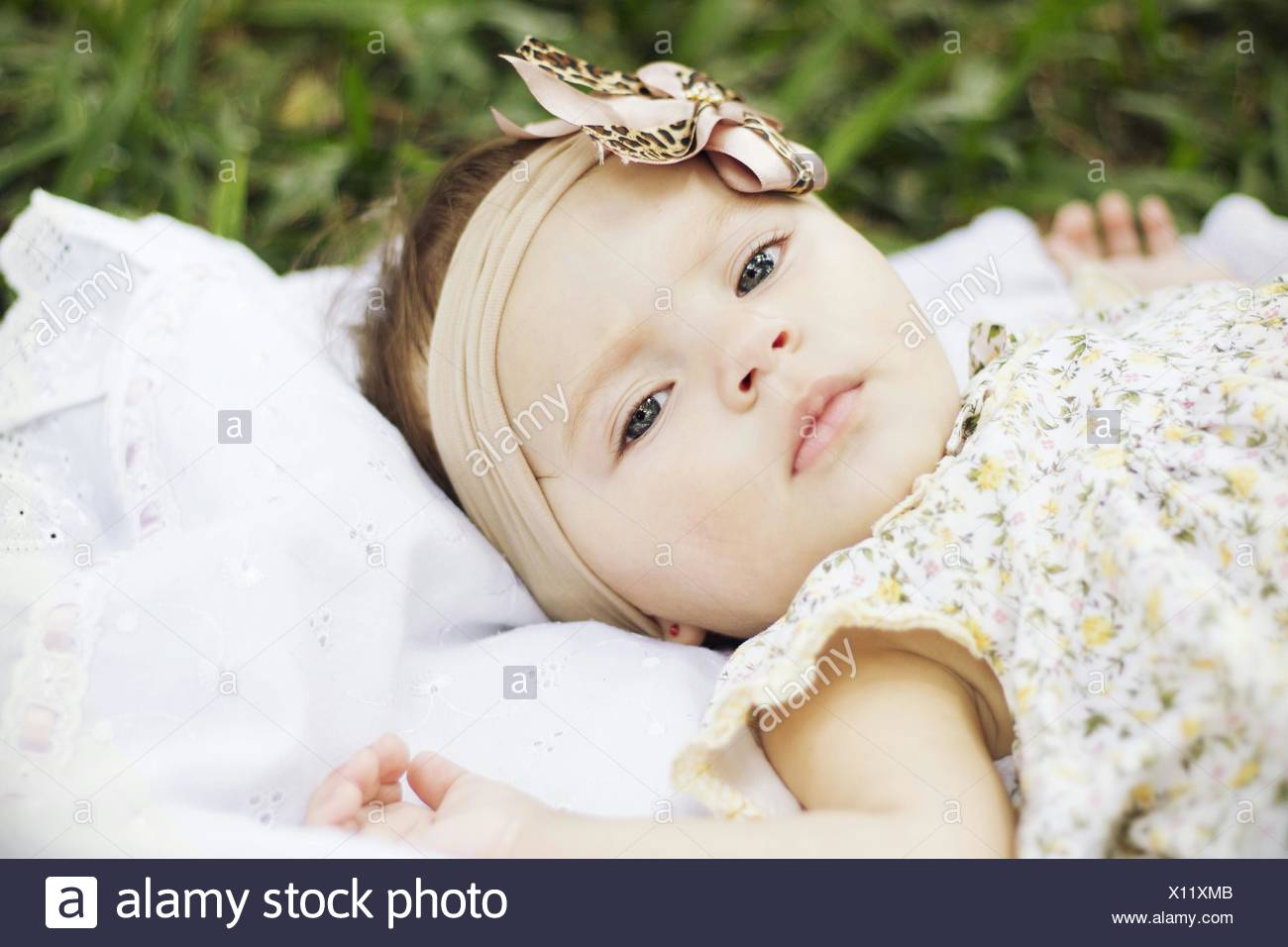 Portrait Of Baby Girl Lying Outdoors - Stock Image