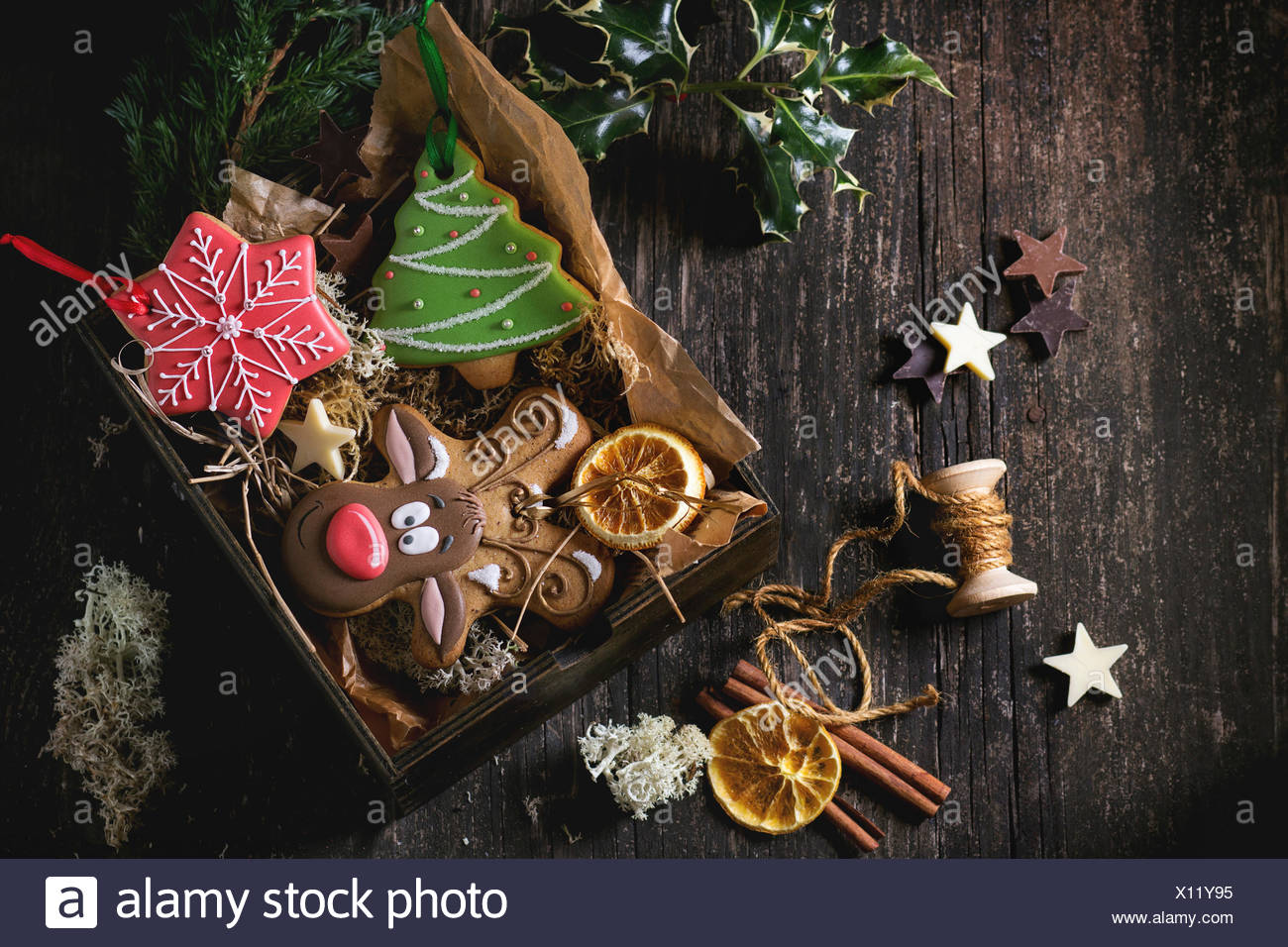 Christmas Handmade patterned gingerbreads as Christmas tree, reindeer Rudolph and snowflake shapes in wooden box over old wooden - Stock Image