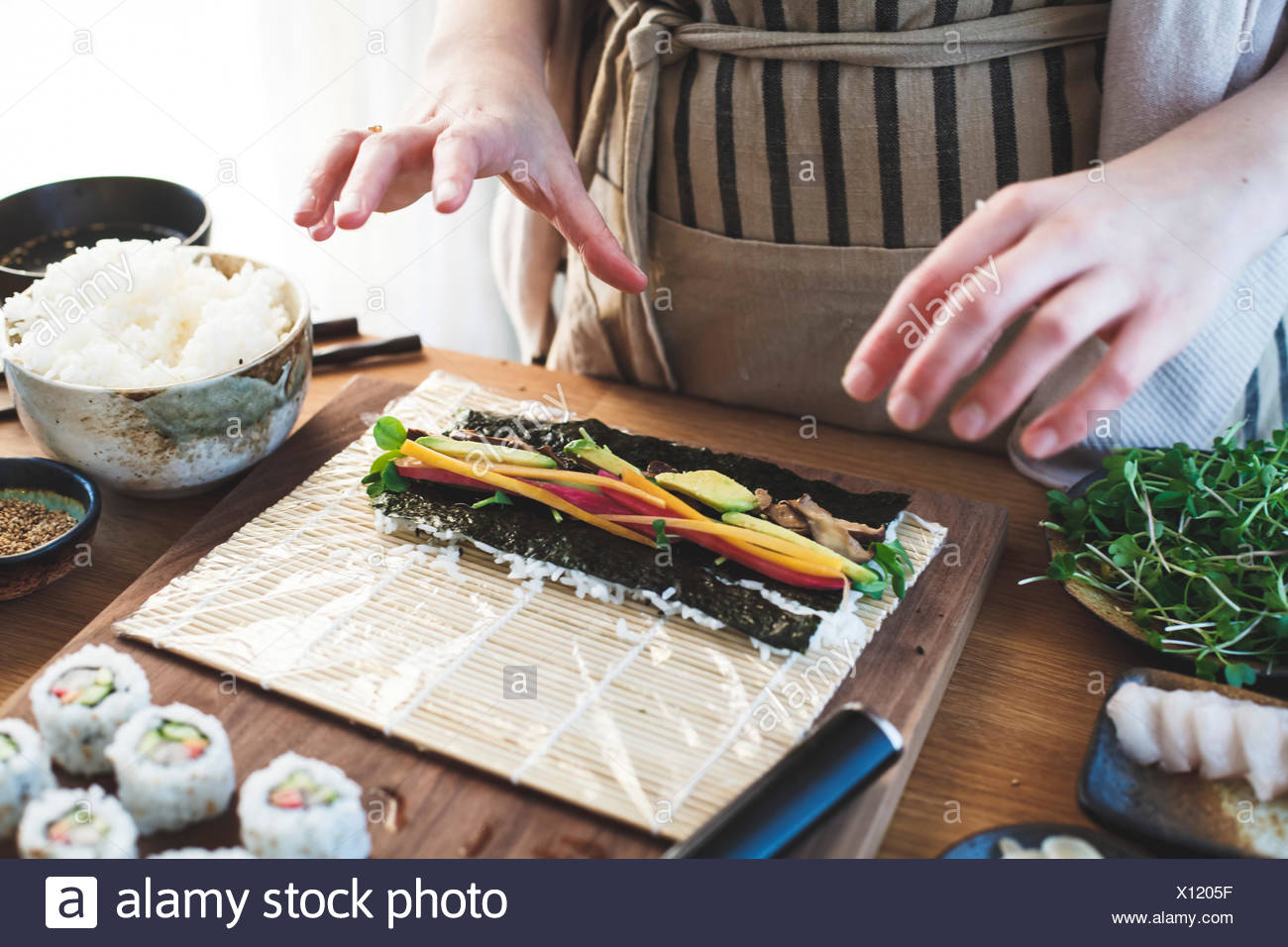 The making of sushi. Rolled sushi preparation. - Stock Image
