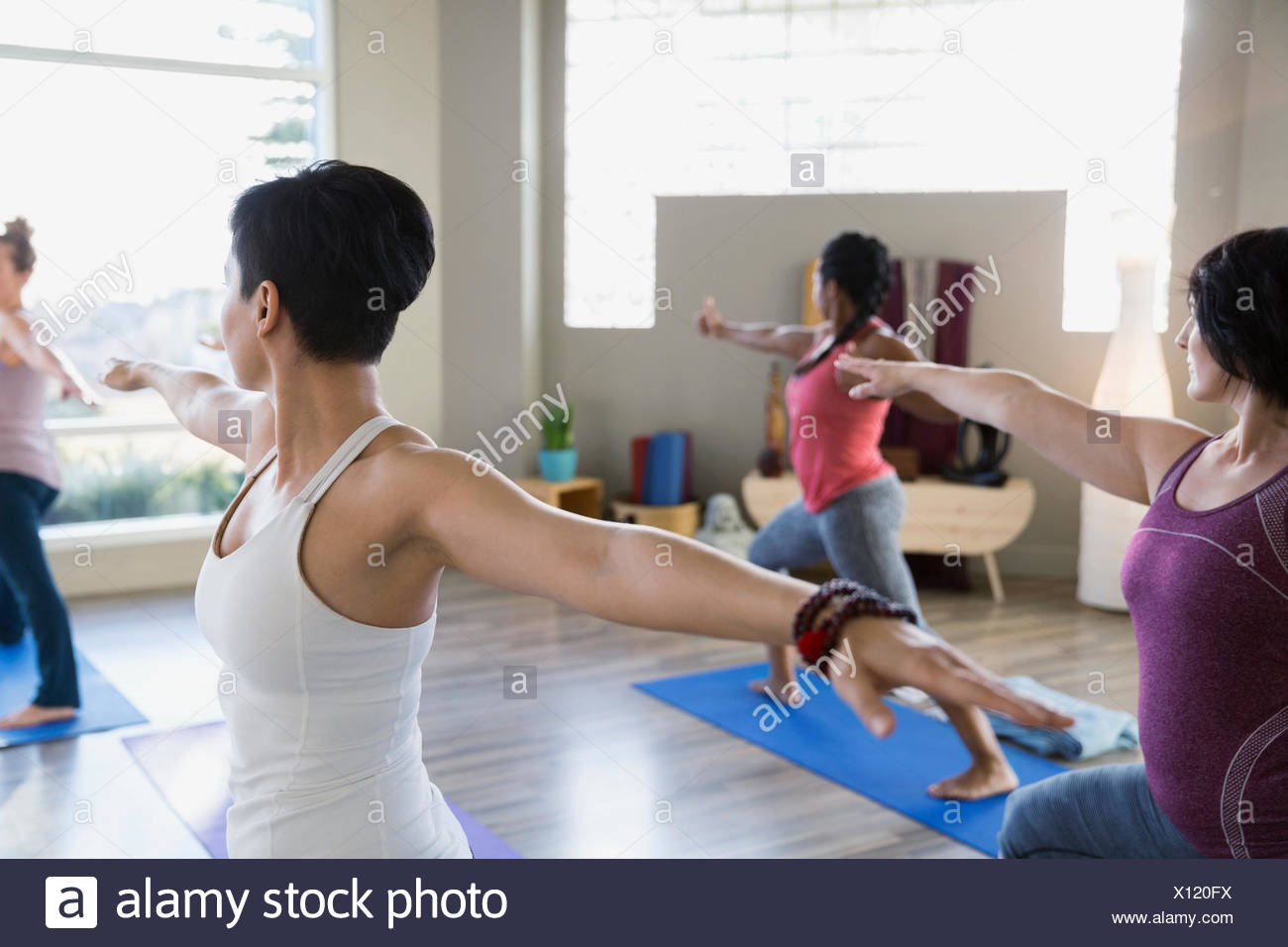 Women practicing warrior 2 pose in yoga class Stock Photo