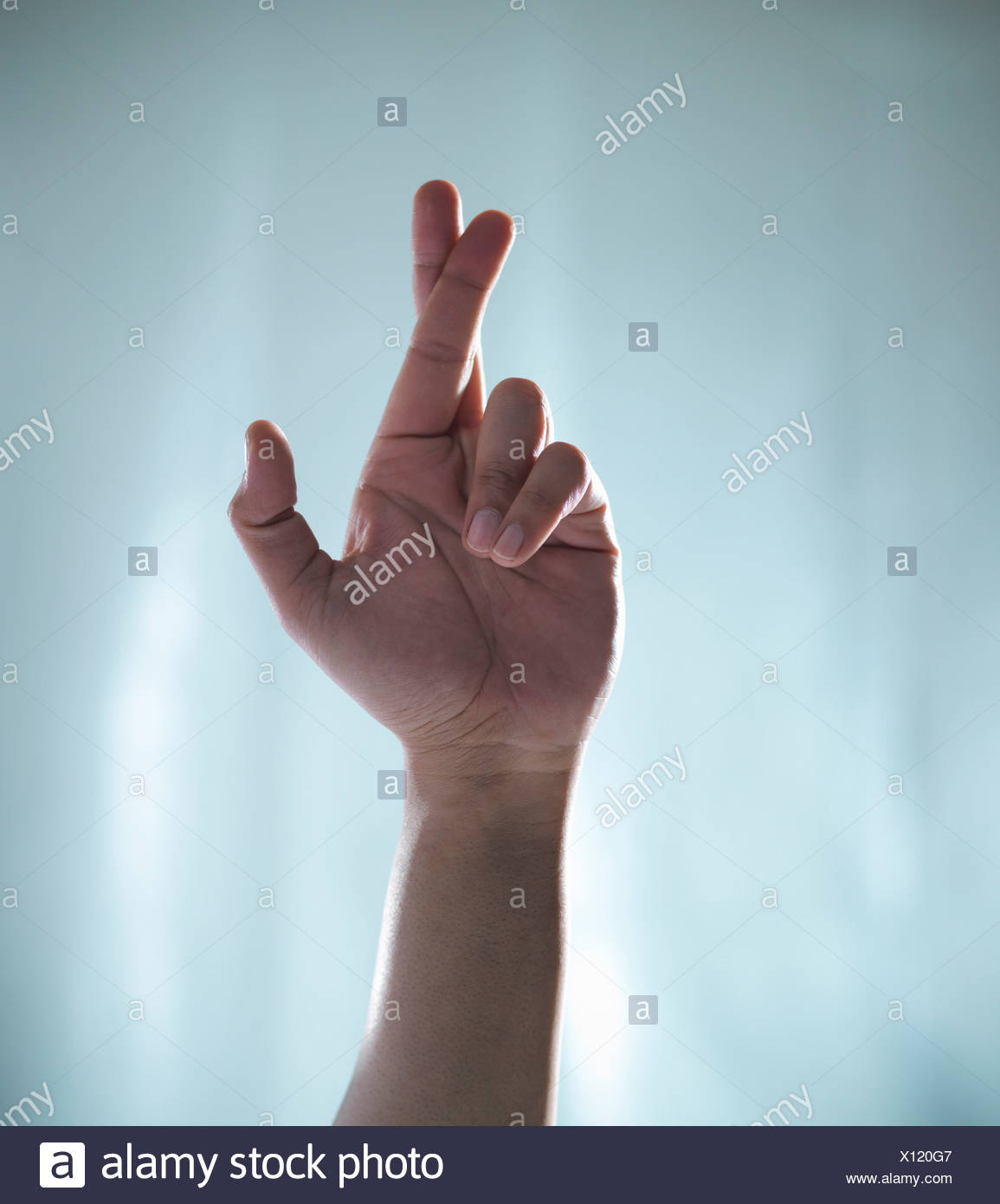 Close up of hand with crossed fingers - Stock Image