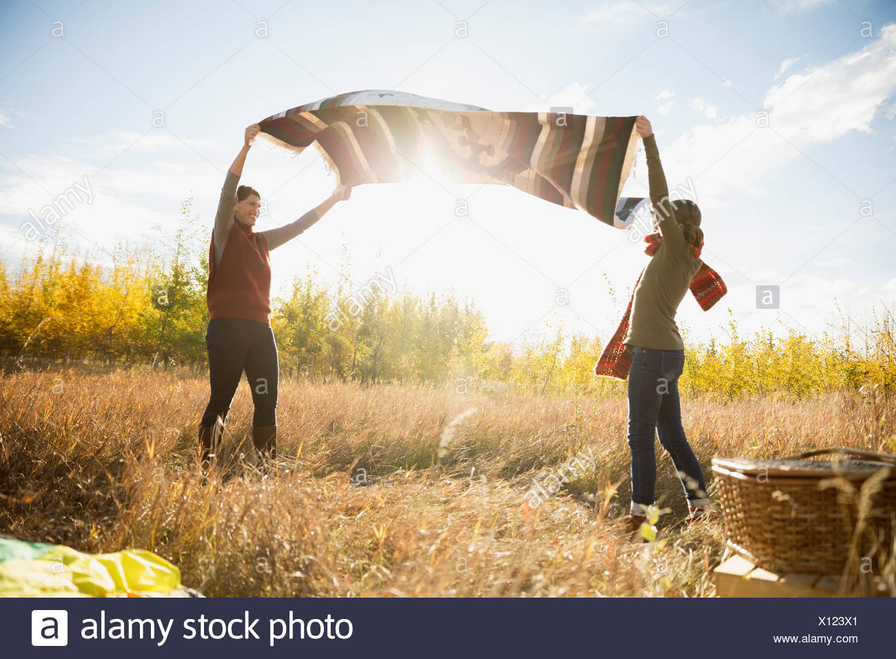Mother and daughter shaking picnic blanket in sunny field - Stock Image