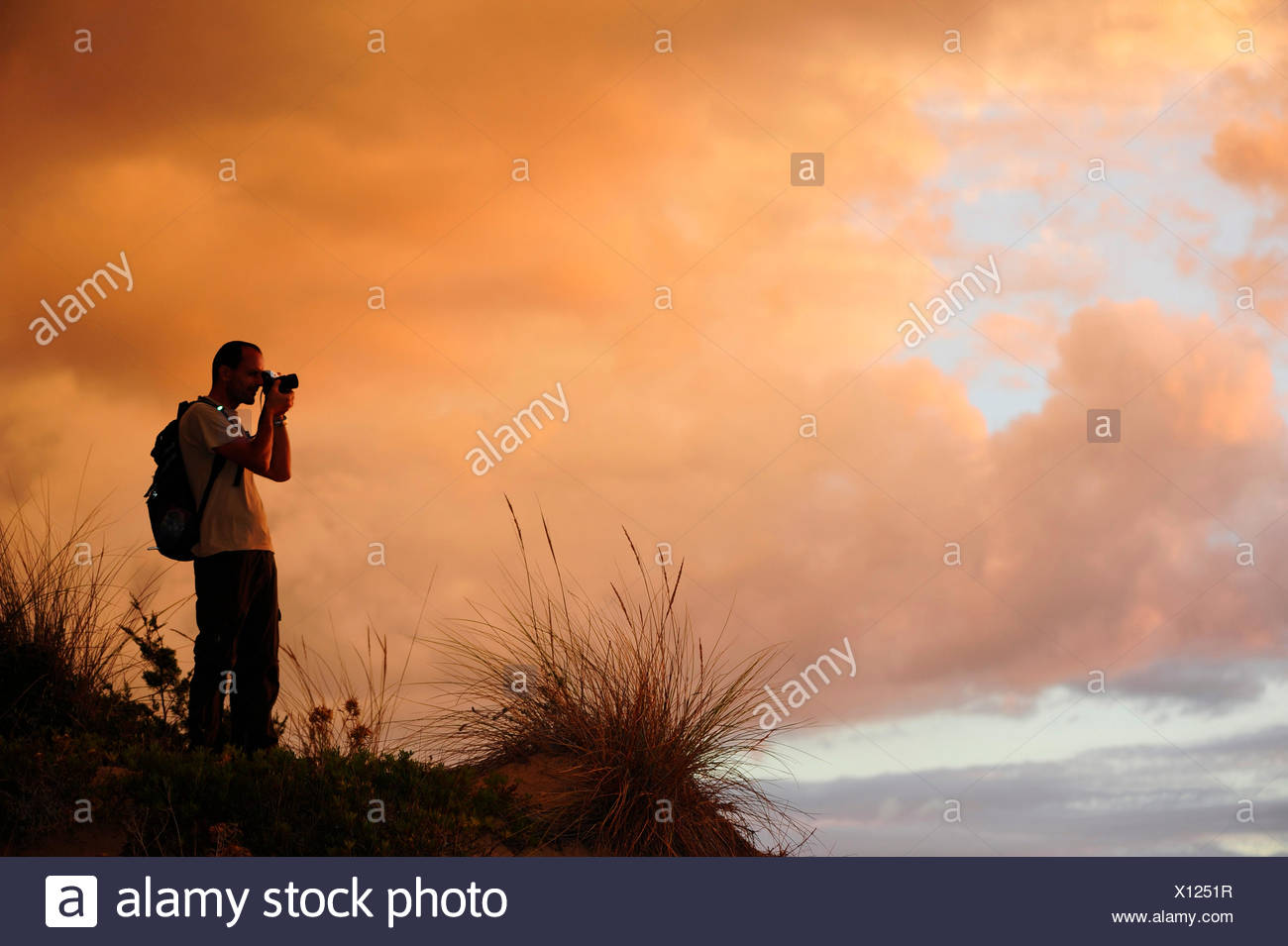 silhouette of a nature photographer in the dunes in the evening glow, Greece, Peloponnese, Messenia Stock Photo