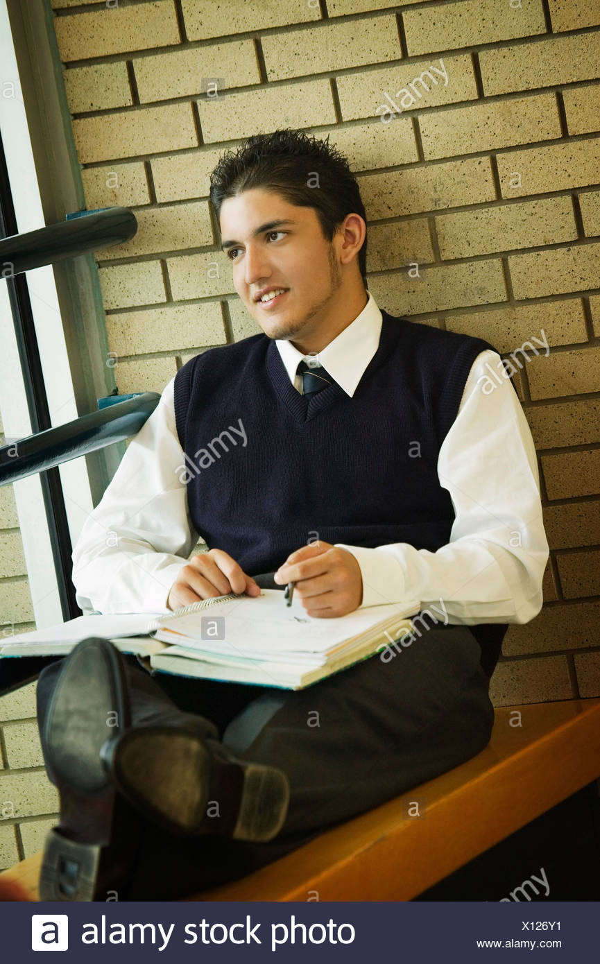 A student in uniform, studying - Stock Image