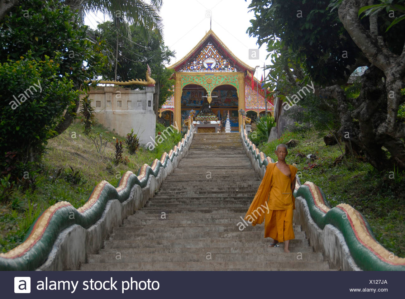 Buddhist monk on the long steps leading to the Wat Jom Khao Manilat temple in Houay Xai, Bokeo Province, Laos, South East Asia - Stock Image