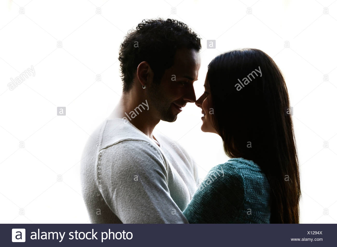 Young couple looking into each other's eyes, backlit, Austria - Stock Image