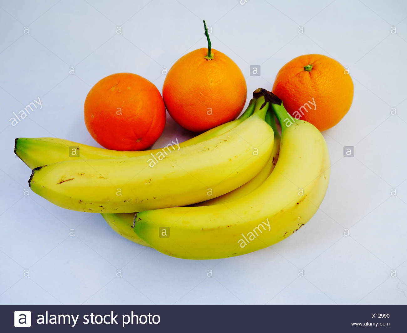High Angle View Of Ripe Bananas And Oranges On White Background - Stock Image