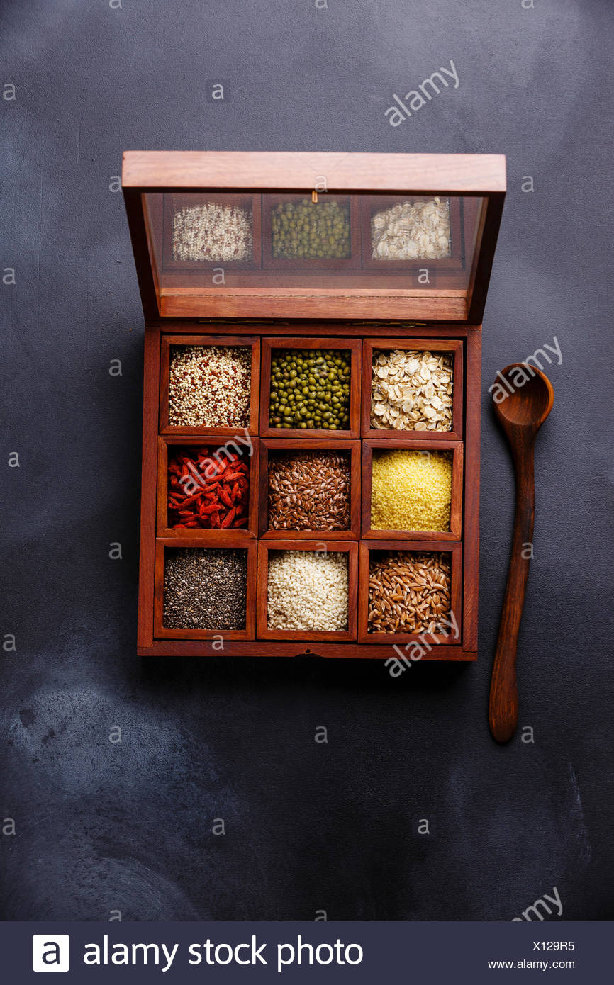 Superfoods and cereals selection in wooden box: oat, mung, quinoa, bulgur, flax seed, goji berry, polba, sesame and chia on dark background - Stock Image