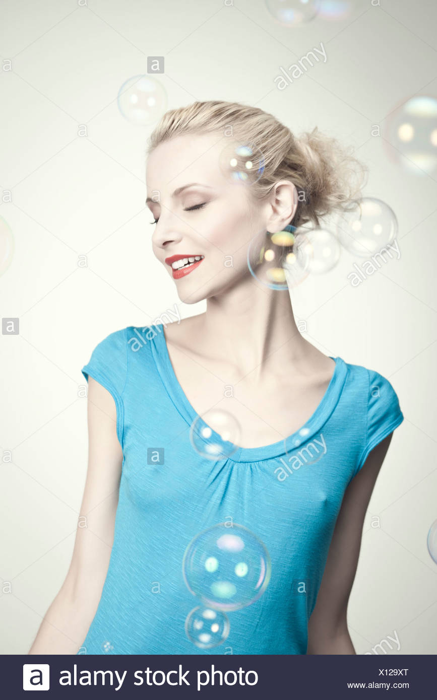 Young woman surrounded by bubbles - Stock Image