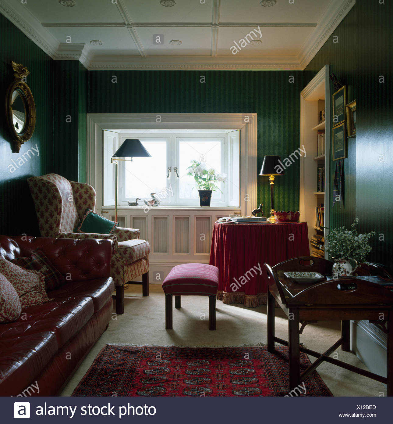 Wing chair and brown leather sofa in dark green living room ...