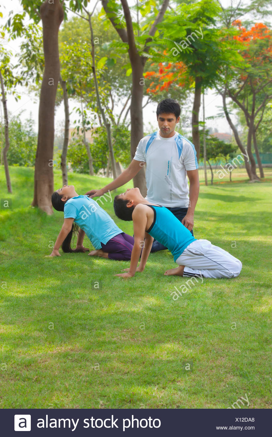 Children exercising as father looks on - Stock Image