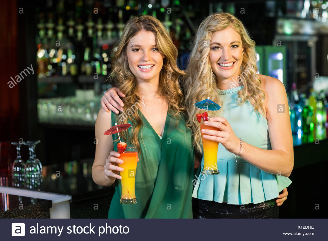 Happy friends drinking cocktails - Stock Image
