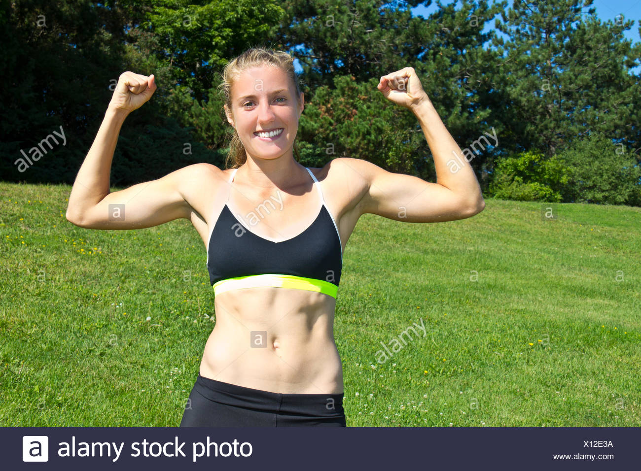 Fit, athletic woman flexing her muscles - Stock Image