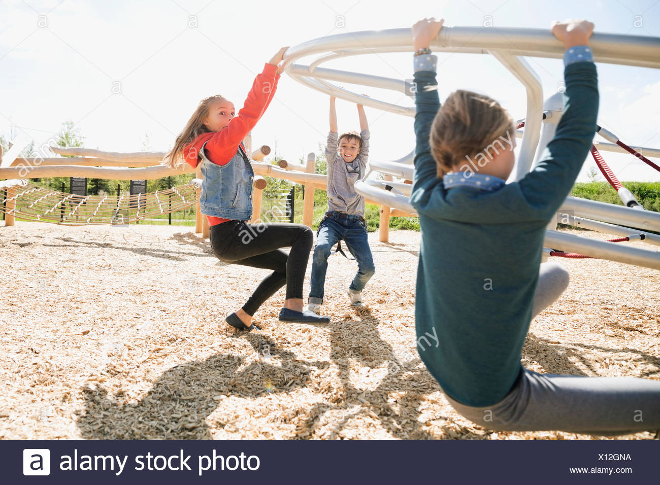Kids hanging from spinning bar at sunny playground - Stock Image